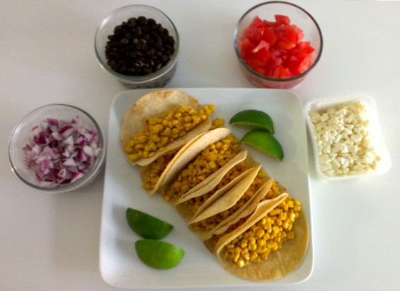 Corn tacos with onions, black beans, tomato, feta, and limes